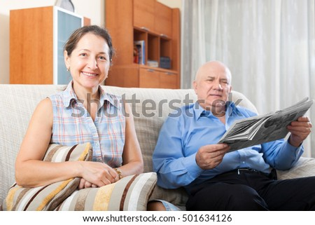 Portrait of smiling happy grandparents on the couch at home with newspaper