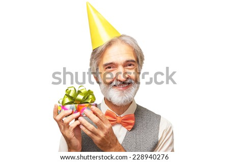 Portrait of smiling happy handsome caucasian aged man with a gray beard and orange bowtie in the yellow festive hood holding small present box in his hands isolated on white background - stock photo