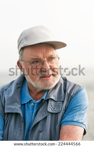 Portrait of smiling happy senior man outdoors looking away - stock photo