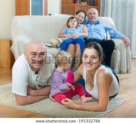 Portrait of smiling happy three generations family sits on parquet floor in livingroom at home