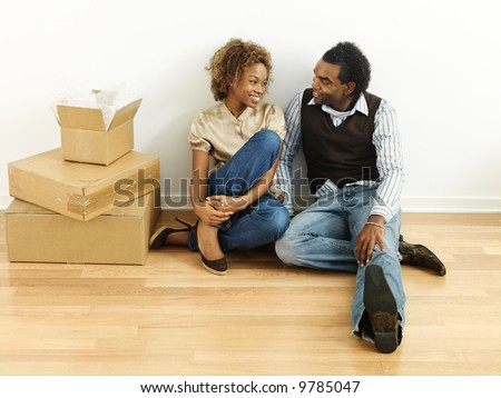 Portrait of smiling happy young couple sitting on floor of home with moving boxes. - stock photo