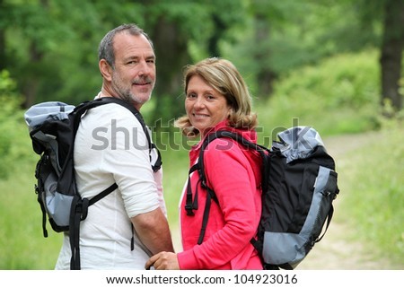Portrait of smiling hikers in forest pathway - stock photo
