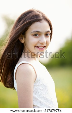 Portrait Of Smiling Hispanic Girl In Countryside