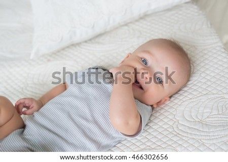 Portrait of smiling infant on a bed