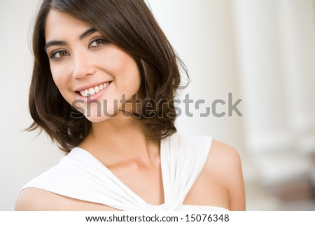Portrait of smiling lady with brown hair on the background of columns - stock photo