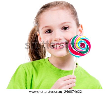 Portrait of smiling little girl in green t-shirt with colored candy - isolated on white. - stock photo