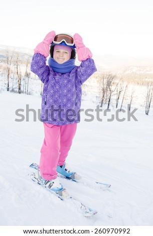 Portrait of smiling little girl on skis  - stock photo