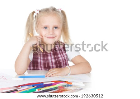 Portrait of smiling little schoolgirl at the desk over white background