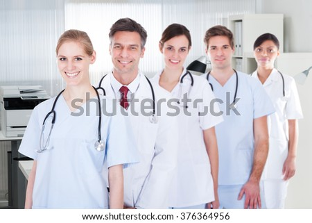 Portrait of smiling male and female doctors standing in row at hospital