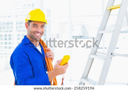 Portrait of smiling male electrician holding multimeter in bright office - stock photo