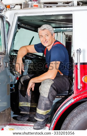 Portrait of smiling male firefighter sitting in truck at fire station - stock photo
