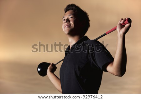 Portrait of smiling male golfer in black shirt posing with driver on shoulders at sunset. - stock photo