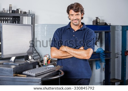 Portrait of smiling male mechanic standing arms crossed by computer in auto repair shop - stock photo