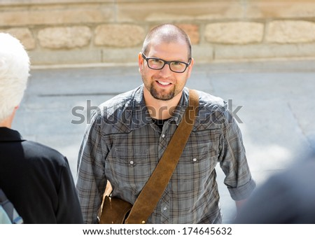 Portrait of smiling male student with bag standing on college campus - stock photo
