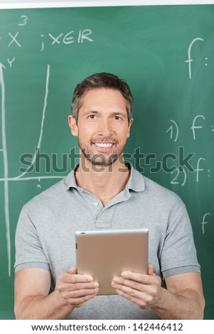 Portrait of smiling male teacher holding digital tablet against chalkboard in classroom