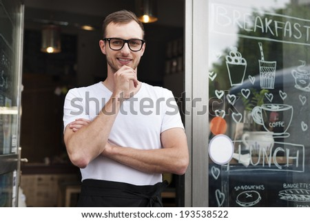 Portrait of smiling male waiter outside the cafe  - stock photo