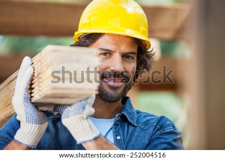 Portrait of smiling male worker carrying tied wooden planks at construction site - stock photo