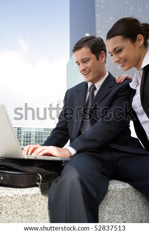 Portrait of  smiling man and woman in front of a laptop computer - stock photo