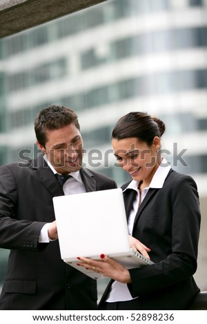 Portrait of smiling man and woman with a laptop computer - stock photo