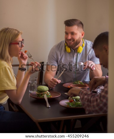 Portrait of smiling man communicating with his friends eating healthy vegan dishes. Happy friends spending their free time in vegan restaurant or cafe. - stock photo