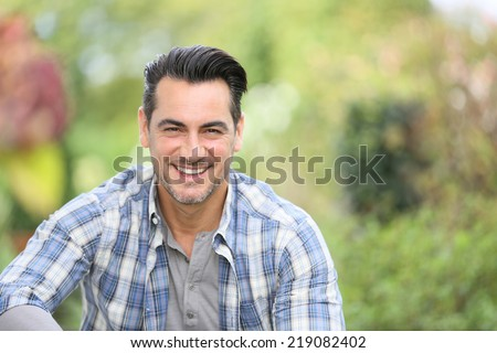 Portrait of smiling man in vegetable garden - stock photo