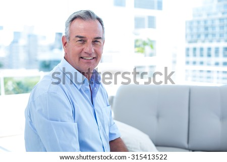 Portrait of smiling man sitting on sofa st home - stock photo