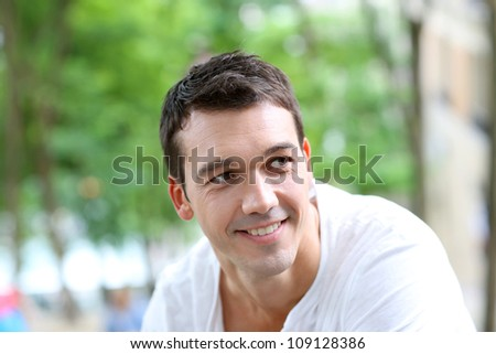 Portrait of smiling man standing in the street - stock photo