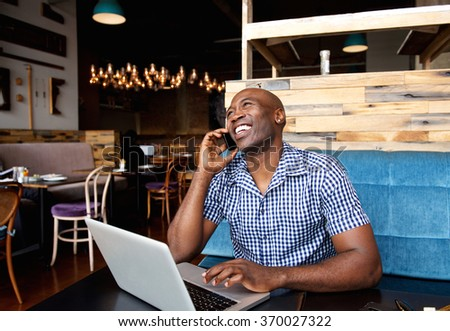 Portrait of smiling man talking on cell phone while sitting at a cafe with a laptop - stock photo
