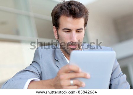 Portrait of smiling man using electronic tablet outside - stock photo