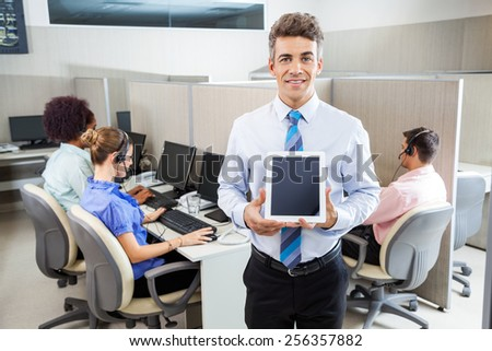 Portrait of smiling manager holding tablet computer while employees working in background at call center - stock photo