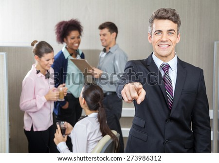 Portrait of smiling manager pointing at you while employees working in background at call center - stock photo