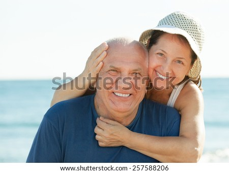 Portrait of smiling mature couple against sea and sky - stock photo