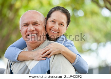 Portrait of smiling mature couple in sweaters at autumn park - stock photo