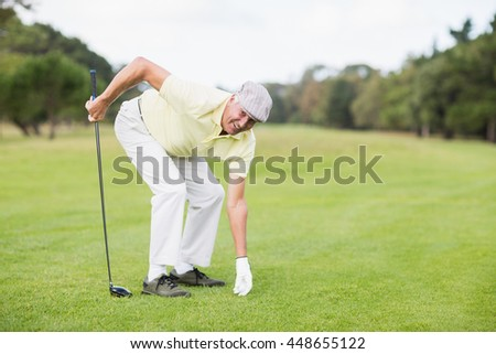 Portrait of smiling mature man holding golf club while bending on grassy field
