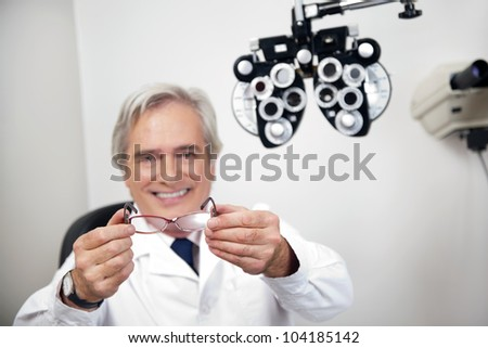 Portrait of smiling mature optometrist holding glasses at the clinic - stock photo