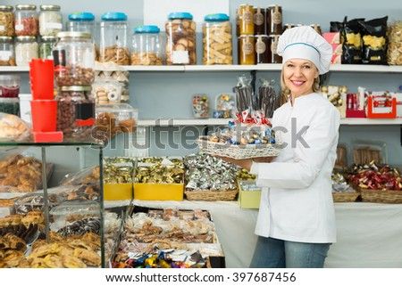 Portrait of smiling mature woman at confectionery display with pastry - stock photo