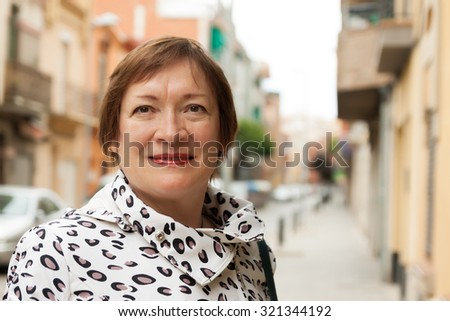 portrait of smiling mature woman at european town street