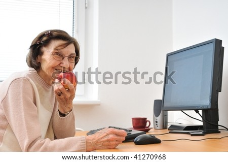 Portrait of smiling mature woman sitting at computer eating apple - stock photo