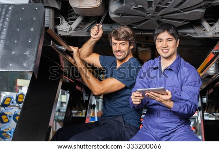 Portrait of smiling mechanics with digital tablet working under lifted car at auto repair shop