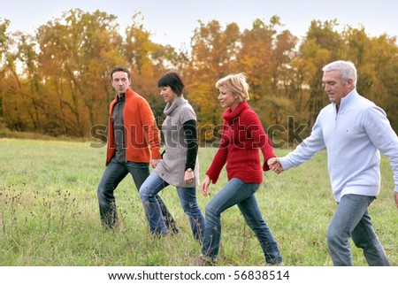 Portrait of smiling men and women having a walk in the countryside - stock photo