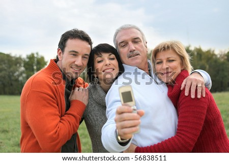 Portrait of smiling men and women in the countryside taking a photo with a mobile phone - stock photo