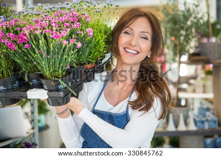 Portrait of smiling mid adult botanist carrying crate full of flower plants in store - stock photo