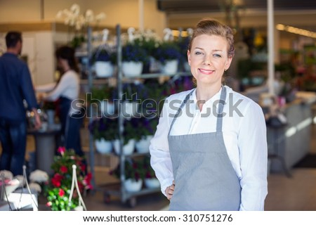 Portrait of smiling mid adult female salesperson at flower shop - stock photo