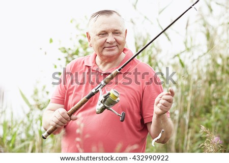 Portrait of smiling middle aged man wearing polo shirt, angling with rod and spinning reel on summer lake - fishing concept - stock photo