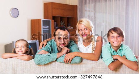Portrait of smiling middle class family with two children at home. Focus on man