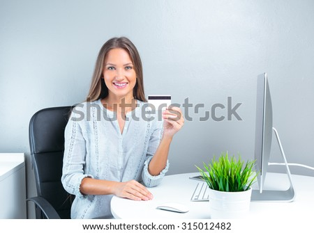 Portrait of smiling modern business woman in office holding credit card - stock photo
