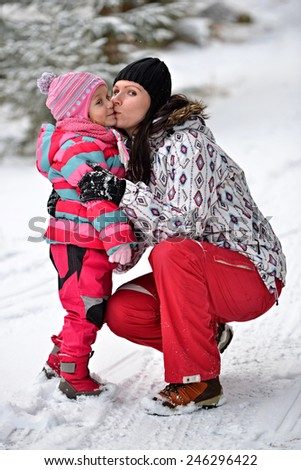 Portrait of smiling mother and baby in winter park  - stock photo