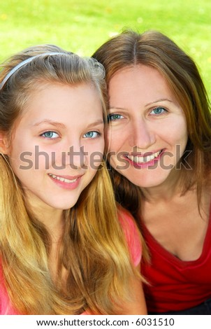 Portrait of smiling mother and daughter in summer park - stock photo