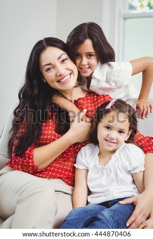 Portrait of smiling mother and daughters sitting at home - stock photo