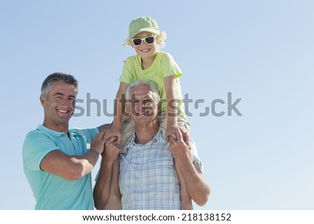 Portrait of smiling multi-generation men against blue sky - stock photo